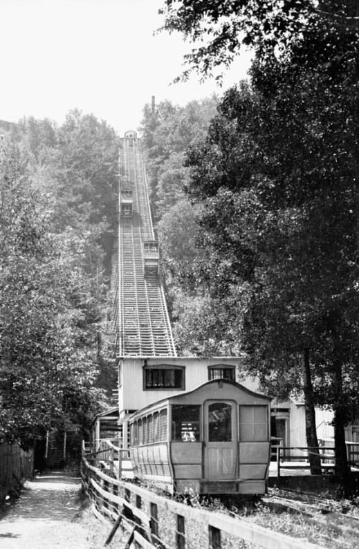 A black-and-white photograph of a funicular. One tram is going up the hill and the other is going down.
