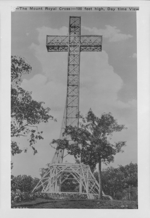 "A black-and-white photograph showing a large metal cross with the text, ""The Mount Royal Cross—100 feet high, daytime view."""