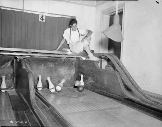 Black and white photograph of a male pinsetter sitting above the alley of a five-pin game as a ball strikes the pins.