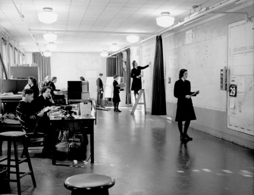 A black-and-white photograph of the interior of a brightly lit plotting room showing a large group of women and several men at work. Figures sit at desks on the left-hand side of the room, while women dressed in dark uniforms examine vast maps attached to the walls on the right-hand side of the room. One woman stands on a short ladder set against the wall and plots information on the upper portion of a map.