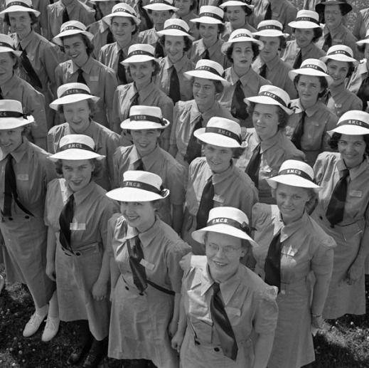 A black-and-white photograph of a crowd of smiling <abbr title=
