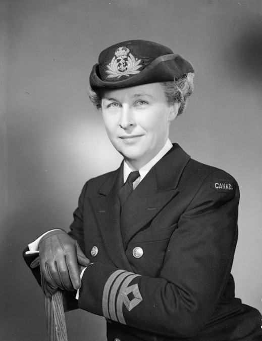 A black-and-white portrait of Adelaide Sinclair, seated with her arms resting on the back of a chair. She is dressed in her naval uniform, including a jacket with a white shirt and dark tie, hat and gloves. She gazes at the viewer with a slight smile on her face.