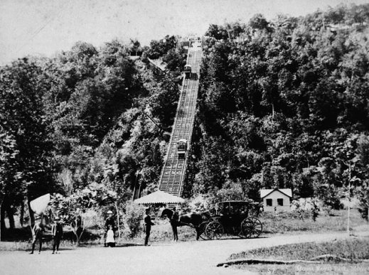 A black-and-white photograph of a funicular going up a densely wooded slope. At the bottom of the hill stands a horse and carriage with a few people standing around looking towards the photographer.