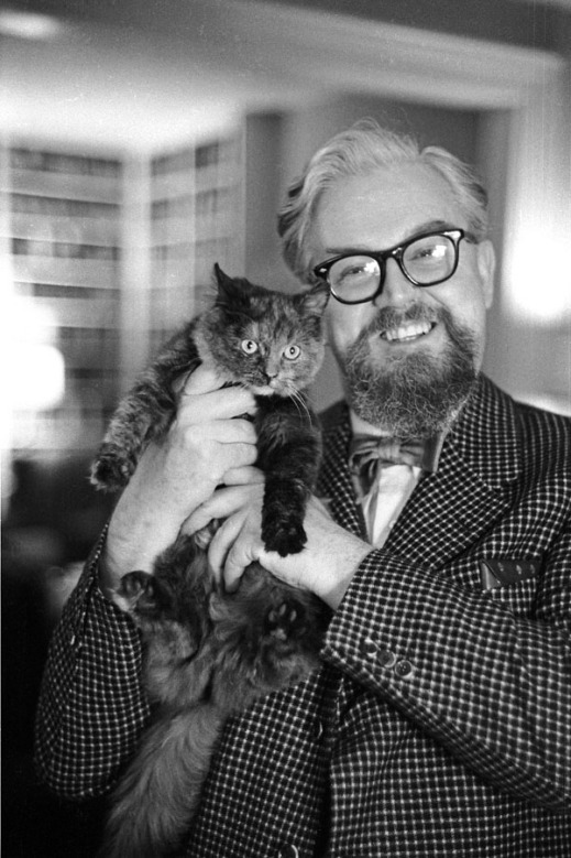 A black-and-white photograph of a man smiling while holding a cat near his shoulder.