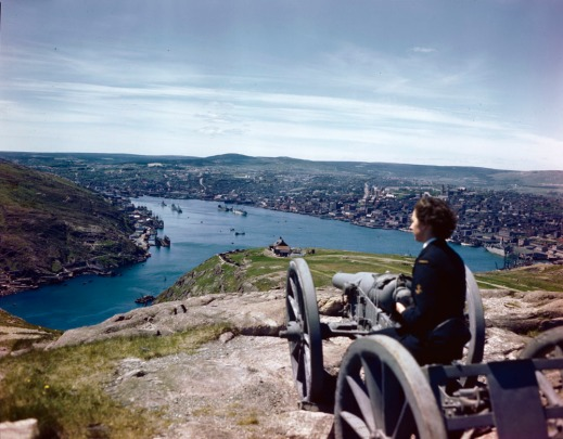 A colour photograph of a member of the WRCNS sitting on top of a 16-pounder canon situated at the top of Signal Hill. Wearing a dark blue uniform, she is turned away from the camera as she gazes on the blue water of St. John's harbour below. The city surrounding the harbour consists of buildings in muted tones and an expanse of low hills are seen in the background. The sky in the top third of the photograph is light blue with a haze of white, wispy clouds.
