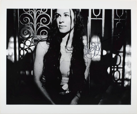 A black-and-white photo of a woman with long hair leaning against a wrought iron fence.