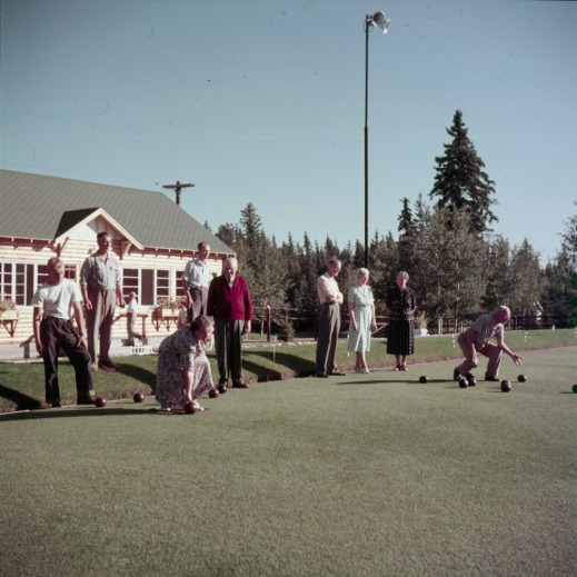 Colour photograph of two lawn bowling teams. A woman and man are both in the midst of throwing their bowls down the lawn.