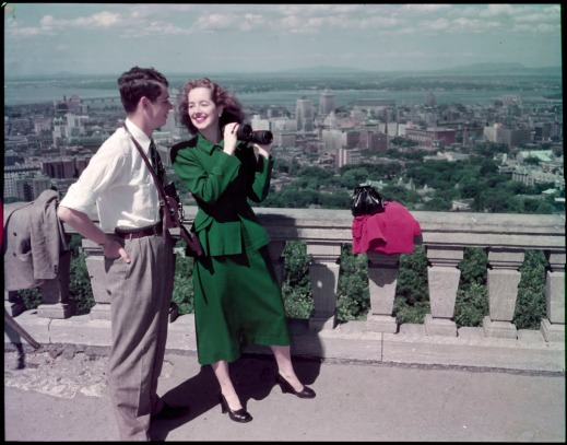 A colour photograph of a couple standing with binoculars looking over the city on the edge of a lookout.