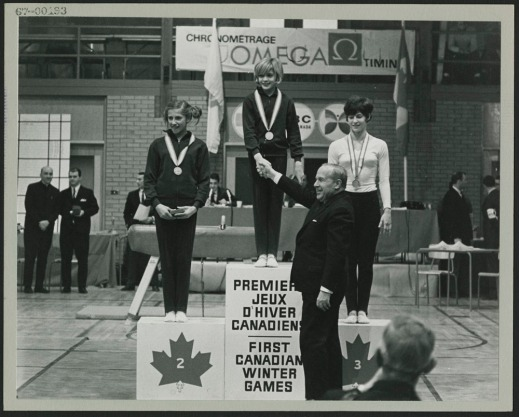 A black-and-white photograph of a podium on which three young women wearing medals are standing. A man is shaking hands with the gold medallist.