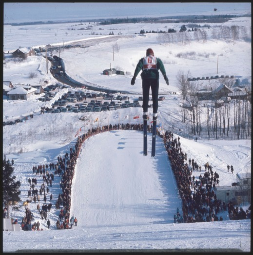 A colour photograph of a ski jumper flying above a crowd of spectators.