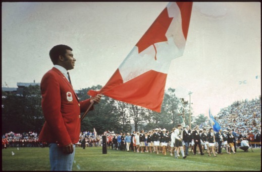 Colour photograph of a man in a red jacket carrying the Canadian flag while athletes enter the stadium.