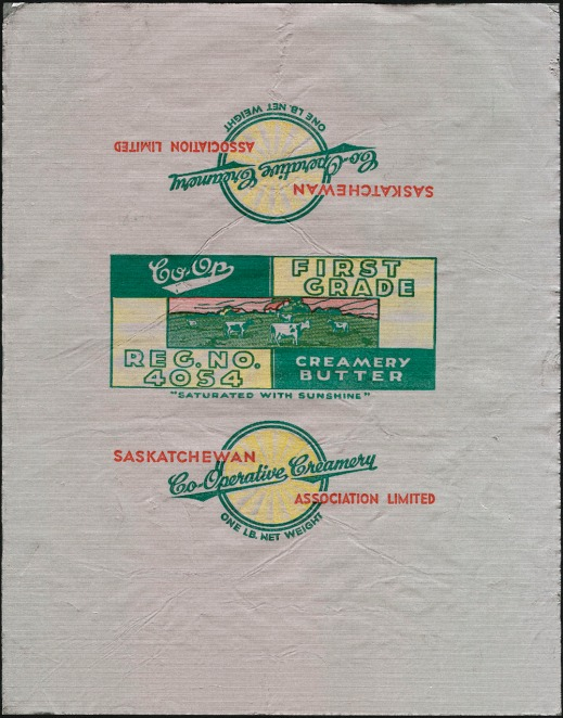 "A colour printed foil wrapper with an image of cows grazing in a meadow. The text reads: ""Co-op. First Grade. Creamery Butter. Reg. No. 4054."" One of the other sides has the following text: ""Saskatchewan Co-Operative Creamery Association Limited. One lb net weight."""