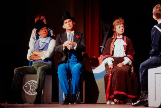 A colour photograph of actors in costume on a stage.