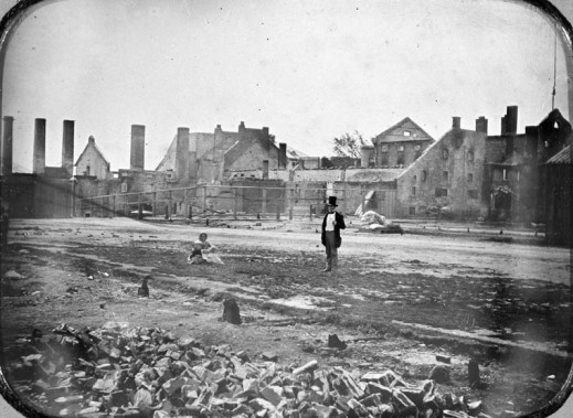 Black-and-white image of rubble in the foreground with a damaged building in the background. A woman with a baby sits in the middle to left of a standing man.¬