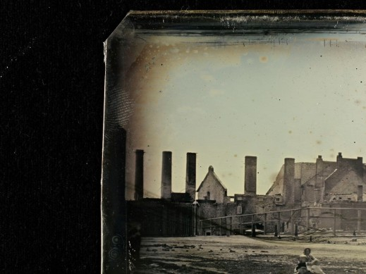 The corner of a daguerreotype showing a fingerprint on the edge of the plate. The plate depicts a closeup of the Molson Brewery after a fire. A woman with a baby is sitting at the bottom edge.