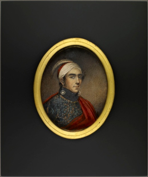 Oval portrait miniature of Major John Norton, Teyoninhokarawen wearing a white and red headdress with an ostrich feather and long earrings with circled stars. He is also wearing a patterned shirt with a red mantle.
