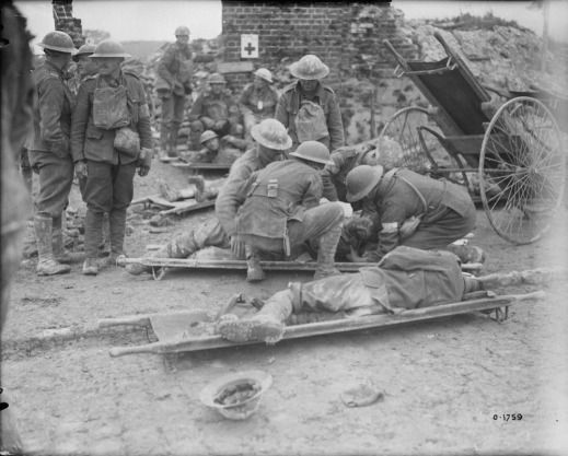 A black-and-white photograph of two men on stretchers. A group of medical personnel is attending to one of the men, while the other man lies on his side. Several soldiers are standing to the left of the stretchers, while others are sitting in the background. The scene is a bombed-out building with only the chimney still standing.