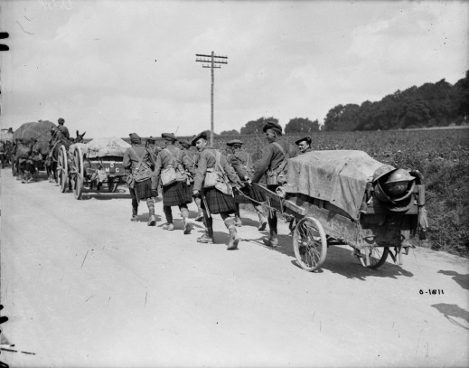 A black-and-white photograph of a convoy of carts moving down the road. A group of Scottish soldiers in full kilt pulls the last cart.