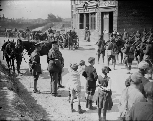A black-and-white photograph of a column of soldiers marching through a town. Onlookers include some officers as well as children and other civilians.