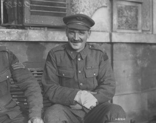 A black-and-white photograph of a seated soldier with a bandaged hand smiling at the photographer.