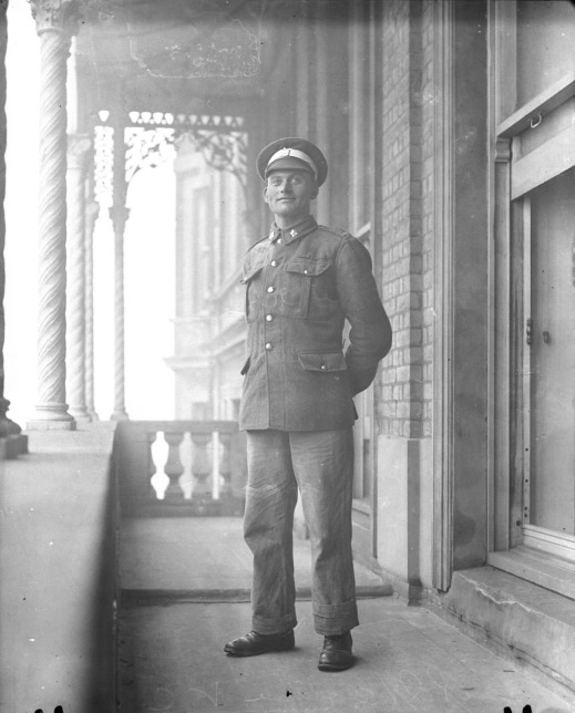 A black-and-white photograph of a young man in uniform standing on a balcony outside.