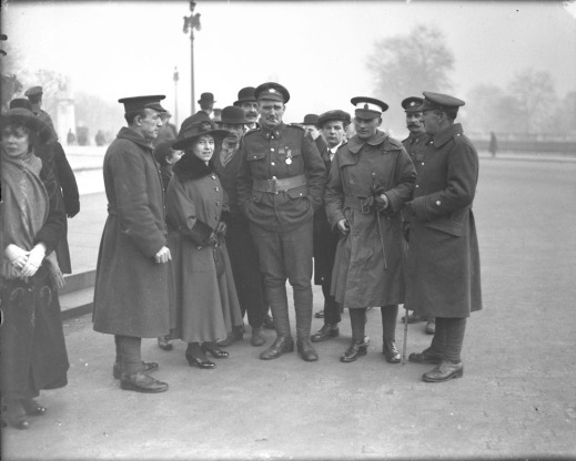 A black-and-white photograph of a group of people gathered around two soldiers.