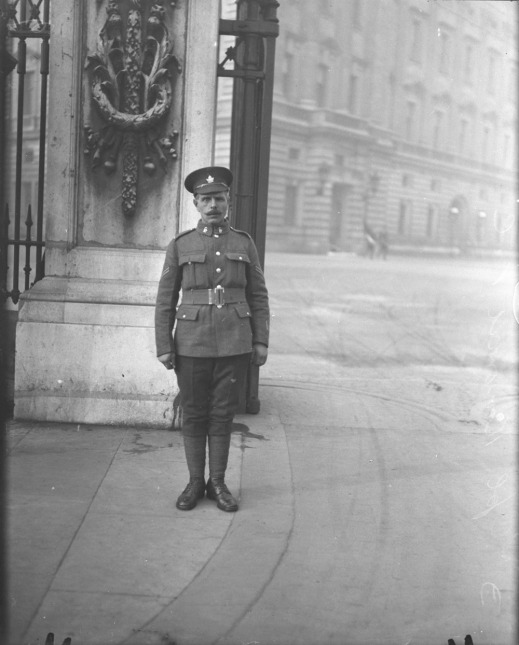 A black-and-white photograph of a soldier wearing a peaked hat adorned with a maple leaf. He is standing at attention in front of a large gate leading into palace grounds.