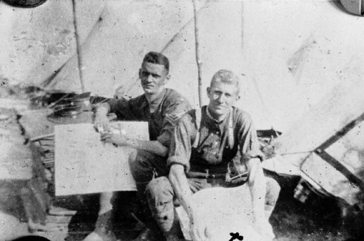 A black-and-white photograph of two young men sitting down in a camp, looking at maps. Behind them can be seen several tents.
