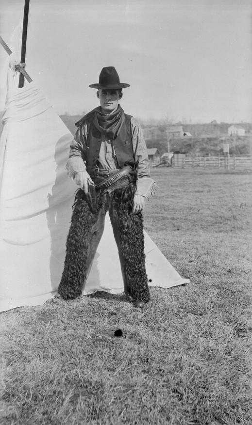 A black-and-white photograph of a cowboy, wearing a black hat, bandana, gloves and fur riding chaps, who stands in front of a tent. His right hand rests on a holstered pistol.
