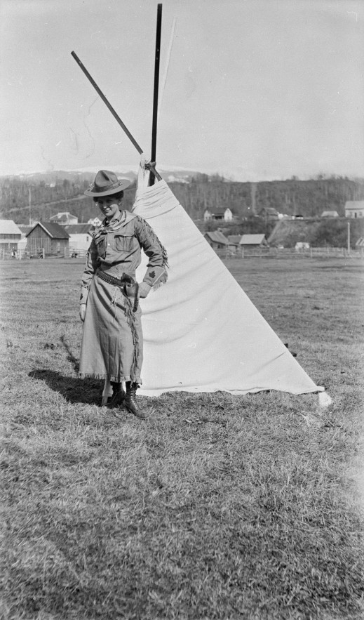 A black-and-white photograph of a cowgirl, wearing a hat, bandana, gloves with stitched maple leaves and a skirt, who stands in front of a tent. Her left hand rests on her left hip and a holstered pistol.