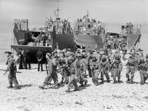 A black-and-white photograph of a practice landing, with soldiers leaving the landing craft and walking on the beach in orderly groups.