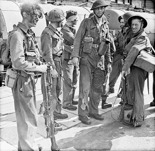 A black-and-white photograph of soldiers, some wounded or with torn uniforms.