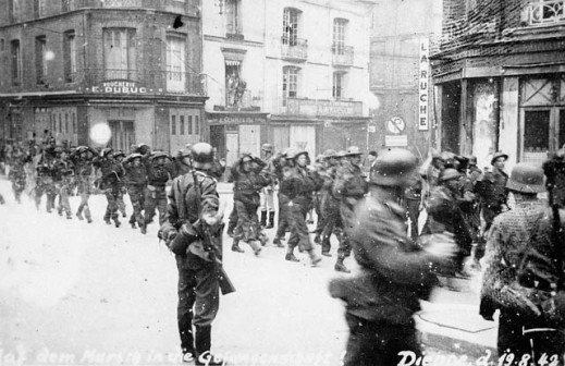 A black-and-white photograph of captured Canadian soldiers being marched in formation through an urban area, with German soldiers guarding them.