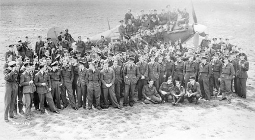 A black-and-white photograph of air force officers standing for a group portrait in front of a Hawker Hurricane fighter aircraft.