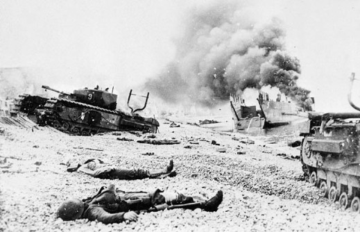 A black-and-white photograph of the bodies of soldiers, a burning landing craft for tanks, and disabled Churchill tanks on a rocky beach.