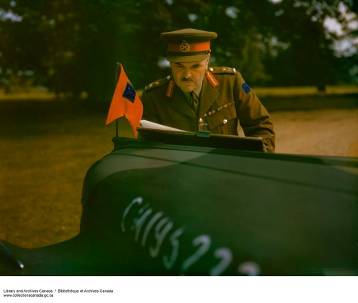 A colour photograph of Major-General J.H. Roberts, in uniform, examining documents on the hood of a staff car.