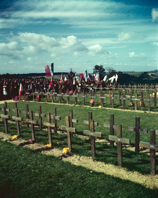 A colour photograph of a ceremony alongside rows of temporary grave crosses at the Dieppe Canadian Military Cemetery near Dieppe, France.