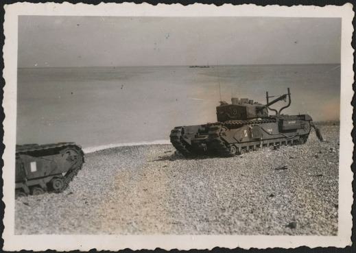 "A black-and-white photograph of disabled or abandoned tanks on the beach at Dieppe. One tank has ""Buttercup"" painted on its side, among other recognition markings."