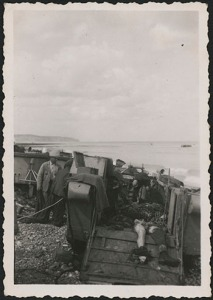 A black-and-white photograph of civilians working amid deceased soldiers in a beached landing craft.