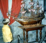 Colour photograph of a young boy peering up at an elaborate model ship
