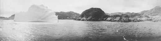 Black-and-white panorama of a large iceberg close to a rocky island shot from a boat.