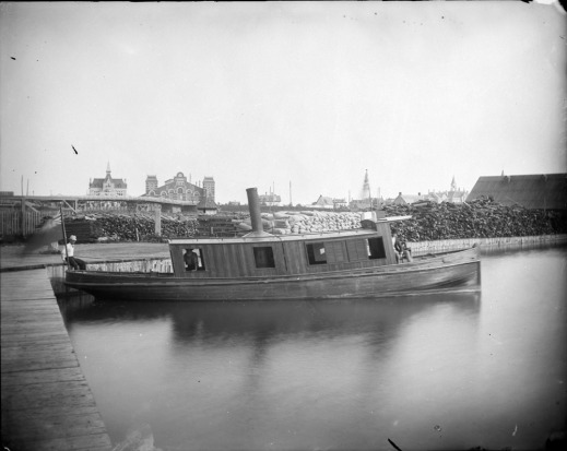 A black-and-white photograph of a small steamboat on the Rideau Canal, with three men located at the stern, midship and bow of the boat, respectively.