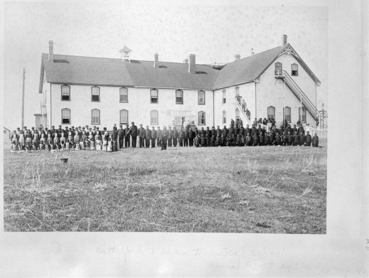 Students in uniform standing in front of the Battleford Indian Industrial School in Battleford, Saskatchewan, 1895.