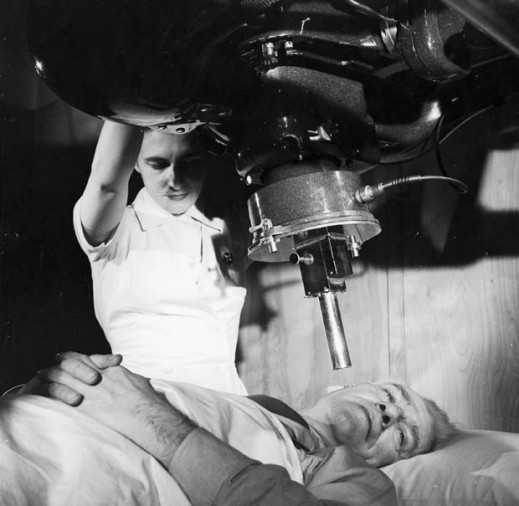 A black-and-white photograph of a nurse positioning an x-ray apparatus over a male patient's right cheek. The patient is lying down on a bed.