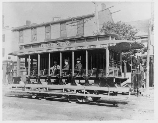 A black-and-white photograph of an open-aired streetcar. There are conductors located at the front and back of the car that has three male passengers sitting, and a boy standing on the sideboard.