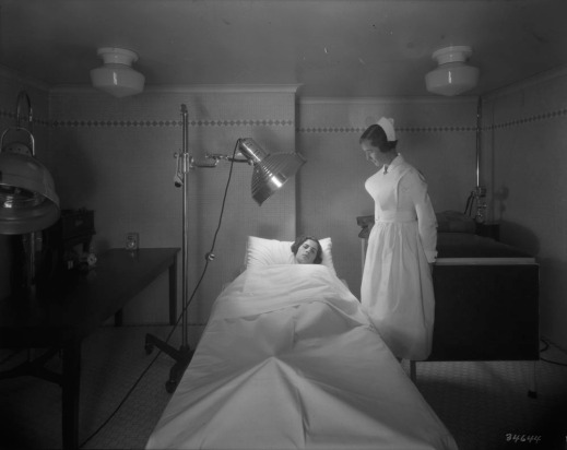A black-and-white photograph of a nurse attending a female patient receiving infrared ray treatment from a lamp. The patient is lying down on a bed.