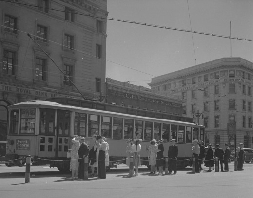 A black-and-white photograph of a lineup of women and men at a pickup location waiting to board an enclosed streetcar.