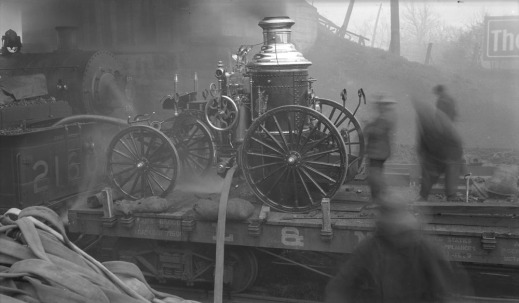 A black-and-white photograph of a steam pumper fire engine on a flatcar, as men use the pump to fight a fire near a rail line and sheds.