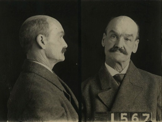 A black-and-white mugshot of a slightly balding man with a moustache seen in profile and straight on.  He holds up a sign with the number 1567.