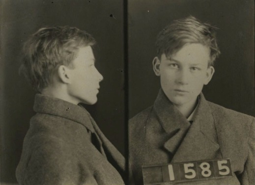A black-and-white mugshot of a very young man seen in profile and straight on. He holds up a sign with the number 1585.